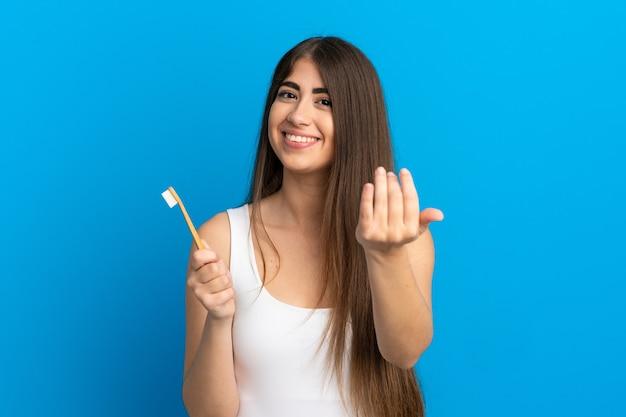 Jovem mulher caucasiana, escovando os dentes isolados sobre um fundo azul, convidando para vir com a mão. feliz que você veio
