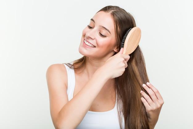 Jovem mulher caucasiana, escovar os cabelos