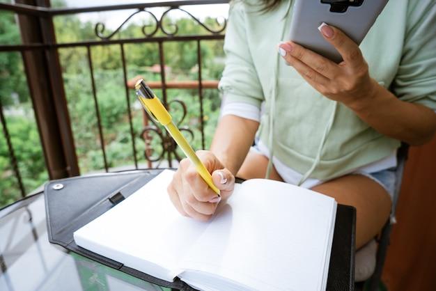 Jovem mulher caucasiana escreve em um caderno com uma caneta em roupas casuais com um telefone na mão em uma varanda de verão