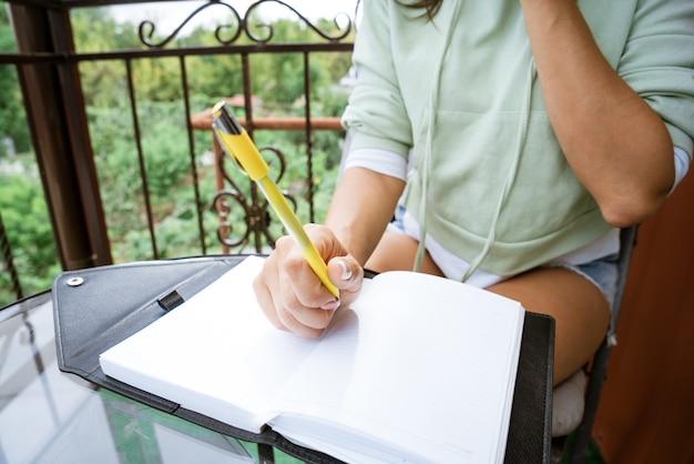 Jovem mulher caucasiana, escreve em um caderno com uma caneta em roupas casuais com um telefone na mão.