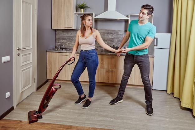 Jovem mulher caucasiana está arrumando cozinha usando aspirador de pó sem fio, homem branco pegou a mão dela, impedindo-a de trabalhar. é assédio sexual no local de trabalho.