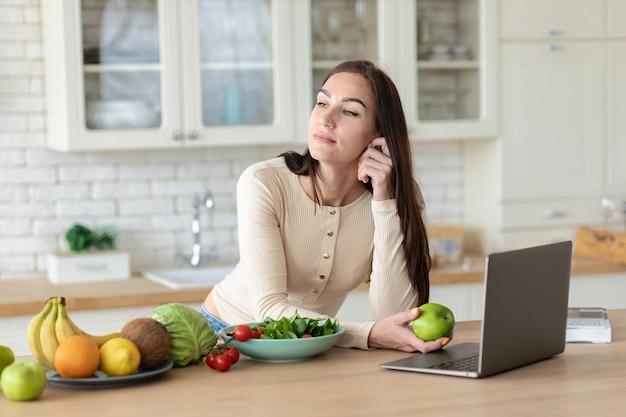 Jovem mulher caucasiana está de pé na cozinha com uma maçã verde nas mãos. estilo de vida saudável e conceito de comida saudável