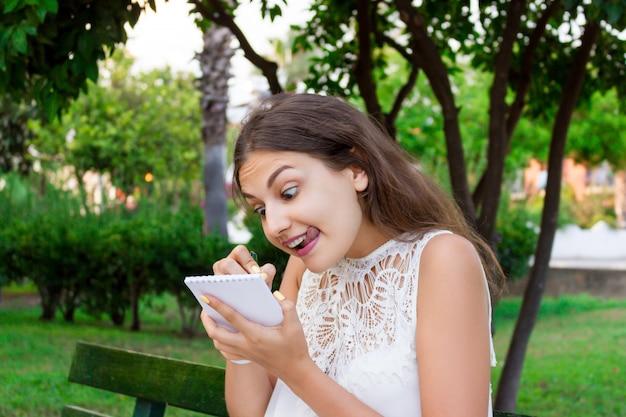 Jovem mulher caucasiana está pensando e anotando suas idéias e pensamentos loucos em um caderno no parque