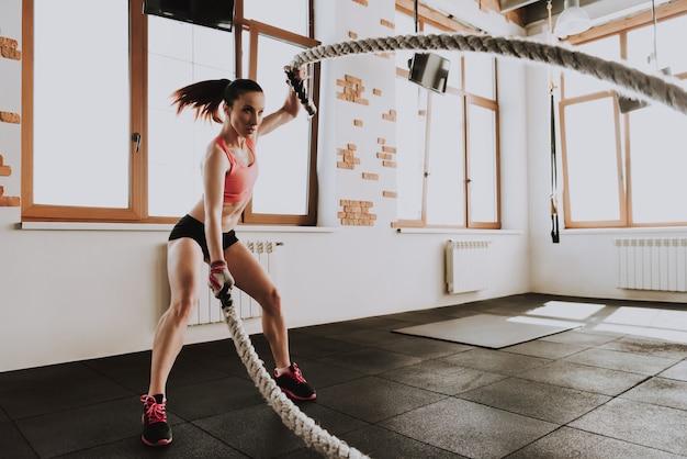 Jovem mulher caucasiana está treinando com cordas