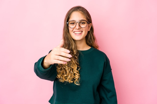Jovem mulher caucasiana, esticando a mão para a câmera em um gesto de saudação.
