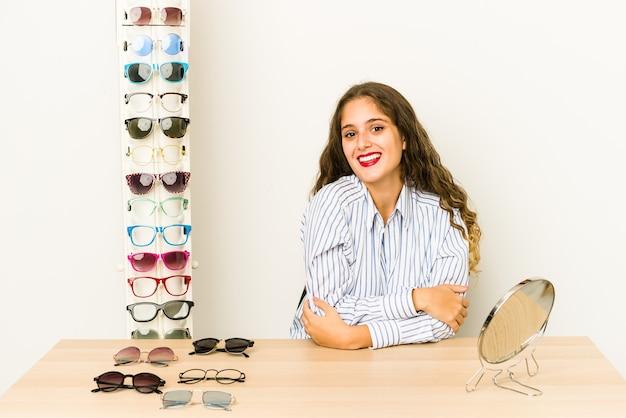 Jovem mulher caucasiana experimentando óculos isolados feliz, sorridente e alegre.