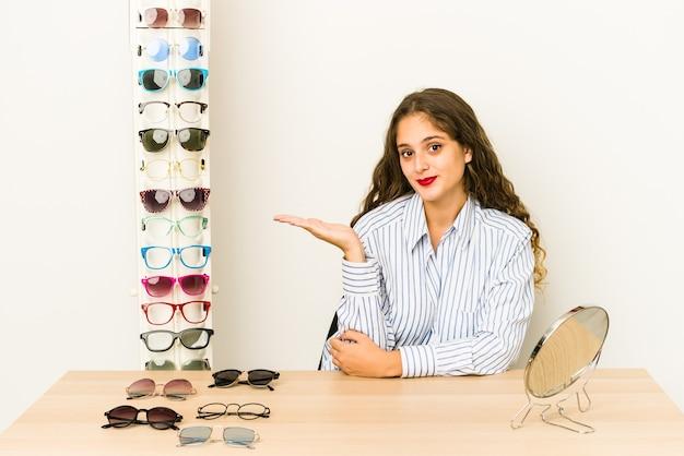 Jovem mulher caucasiana experimentando óculos isolados, mostrando um espaço de cópia na palma da mão e segurando a outra mão na cintura.