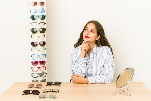 Jovem mulher caucasiana experimentando óculos isolados olhando de soslaio com expressão duvidosa e cética.