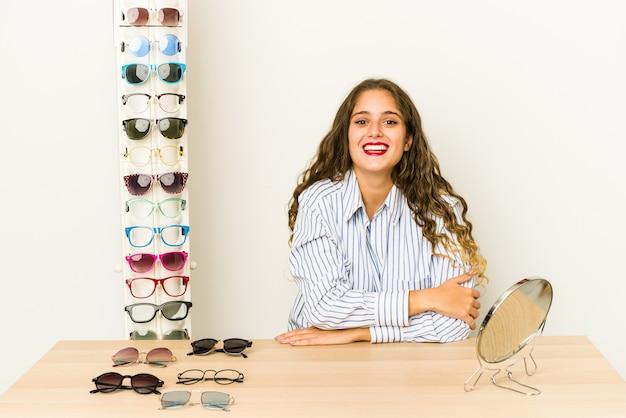 Jovem mulher caucasiana, experimentando óculos isolados, rindo e se divertindo.