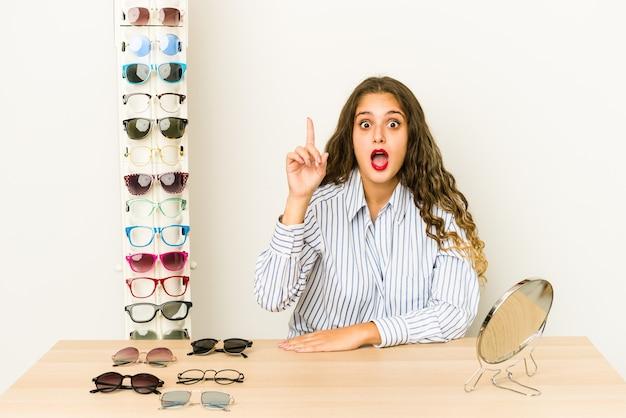 Jovem mulher caucasiana, experimentando óculos isolados, tendo uma ideia, o conceito de inspiração.