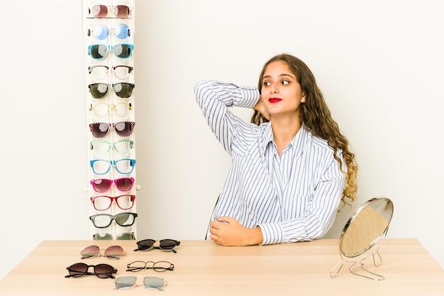 Jovem mulher caucasiana experimentando óculos isolados tocando a parte de trás da cabeça, pensando e fazendo uma escolha.