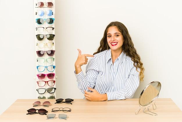 Jovem mulher caucasiana experimentando óculos pessoa isolada apontando com a mão para um espaço de cópia de camisa, orgulhosa e confiante