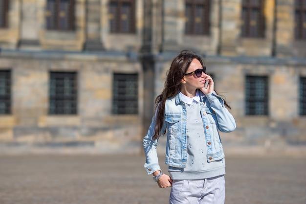 Jovem mulher caucasiana, falando por telefone celular em ruas antigas da cidade europeia