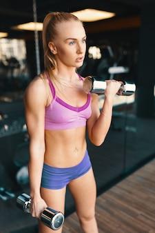 Jovem mulher caucasiana, fazendo exercícios com halteres enquanto treina os braços no ginásio