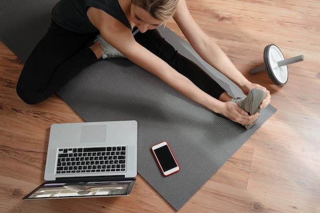Jovem mulher caucasiana fazendo exercícios online e repetindo exercícios de treinamento online no laptop