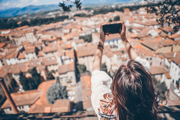 Jovem mulher caucasiana fazendo foto pelo celular do lugar de observação