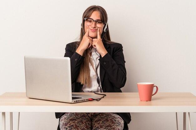 Jovem mulher caucasiana fazendo teletrabalho isolado no fundo branco, duvidando entre duas opções.