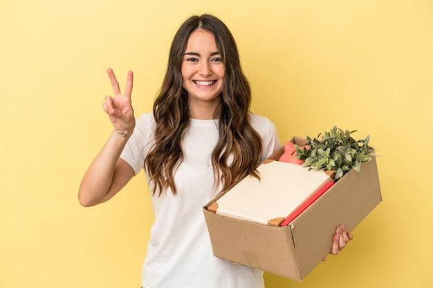 Jovem mulher caucasiana, fazendo um movimento isolado em um fundo amarelo, mostrando o número dois com os dedos.