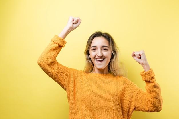 Jovem mulher caucasiana feliz, com um suéter laranja, levanta o punho cerrado de alegria
