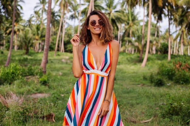 Jovem mulher caucasiana feliz em um vestido de verão listrado colorido com cabelo curto e encaracolado em óculos de sol férias no quente país exótico.
