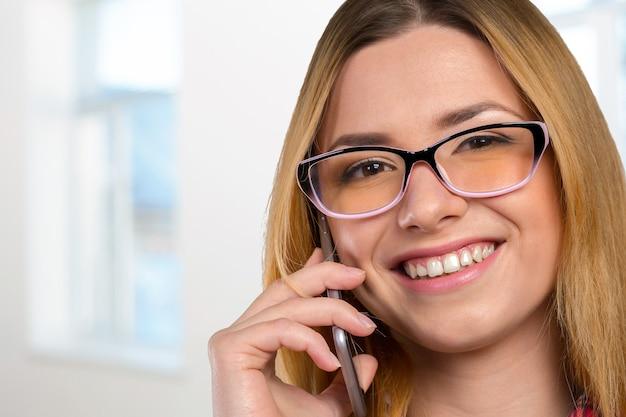 Jovem mulher caucasiana feliz está ligando com um telefone celular