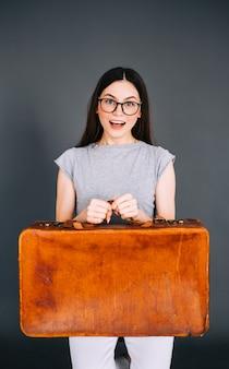 Jovem mulher caucasiana feliz segurando a bagagem de viagem isolada no fundo cinza. pronto para viajar