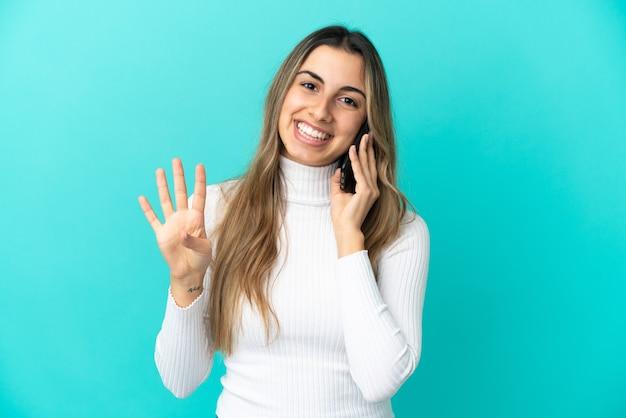 Jovem mulher caucasiana feliz usando telefone celular isolado em um fundo azul e contando quatro com os dedos