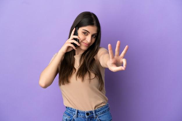 Jovem mulher caucasiana feliz usando telefone celular isolado em um fundo roxo e contando três com os dedos