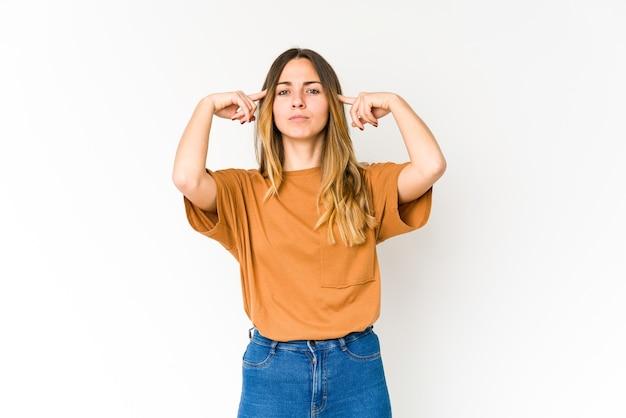 Jovem mulher caucasiana focada em uma tarefa, mantendo os indicadores apontando a cabeça.