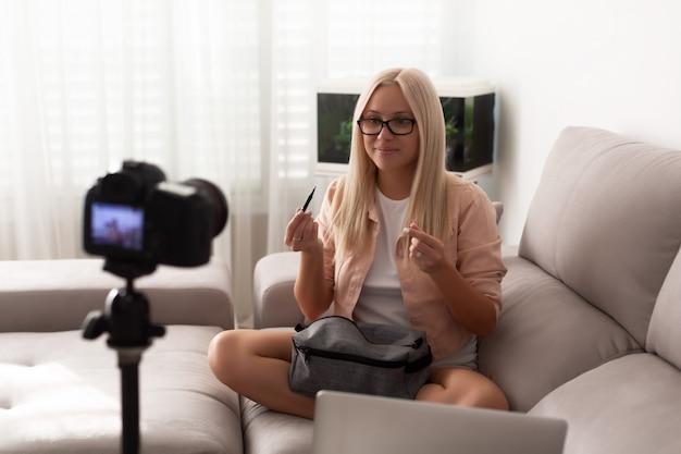 Jovem mulher caucasiana, gravação de blog de vídeo na câmera
