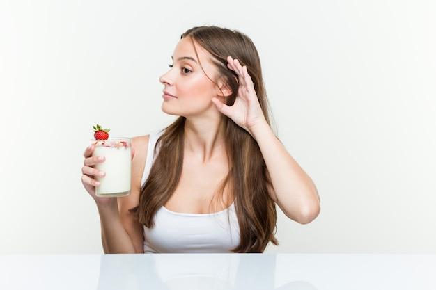 Jovem mulher caucasiana holdingsmoothie tentando ouvir uma fofoca.