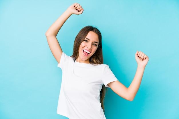 Jovem mulher caucasiana isolada comemorando um dia especial, saltos e levante os braços com energia.