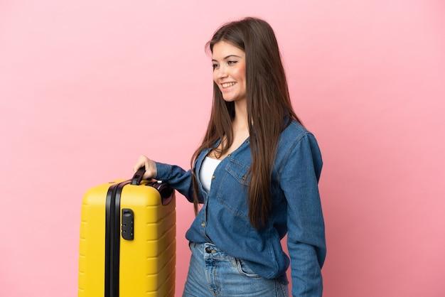 Jovem mulher caucasiana isolada de férias com mala de viagem