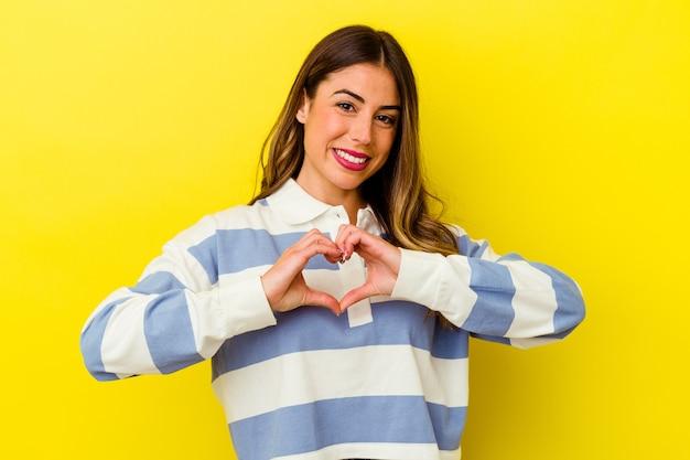 Jovem mulher caucasiana isolada em amarelo sorrindo e mostrando uma forma de coração com as mãos.