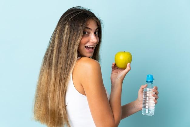 Jovem mulher caucasiana isolada em azul com uma maçã e uma garrafa de água