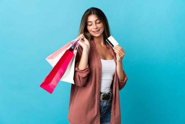Jovem mulher caucasiana isolada em azul segurando sacolas de compras e um cartão de crédito