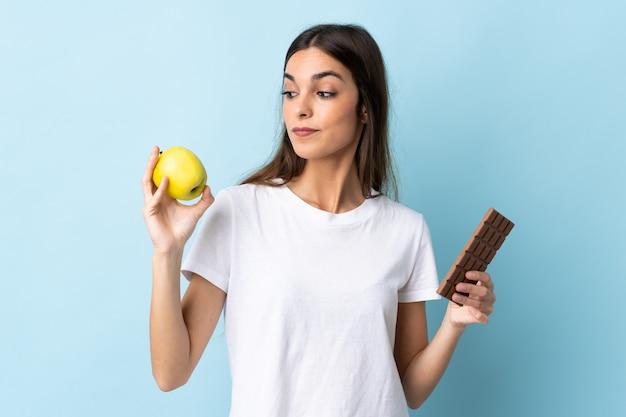 Jovem mulher caucasiana isolada em azul tendo dúvidas enquanto toma um comprimido de chocolate em uma mão e uma maçã na outra
