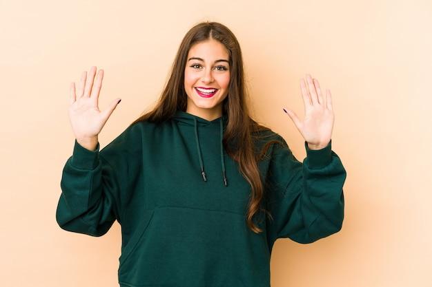 Jovem mulher caucasiana isolada em bege mostrando a tonelada de número com as mãos.