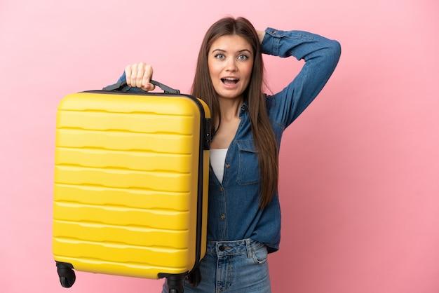 Jovem mulher caucasiana isolada em férias com mala de viagem e surpresa