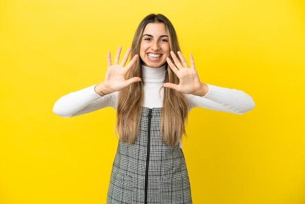 Jovem mulher caucasiana isolada em fundo amarelo contando dez com os dedos