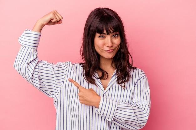 Jovem mulher caucasiana isolada em fundo rosa mostrando força gesto com os braços, símbolo do poder feminino