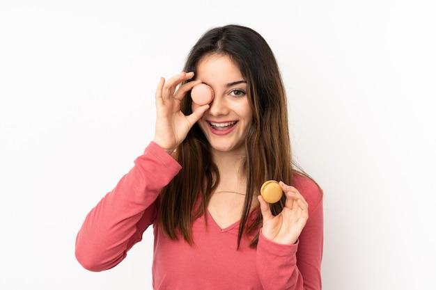 Jovem mulher caucasiana isolada em rosa segurando macarons franceses coloridos