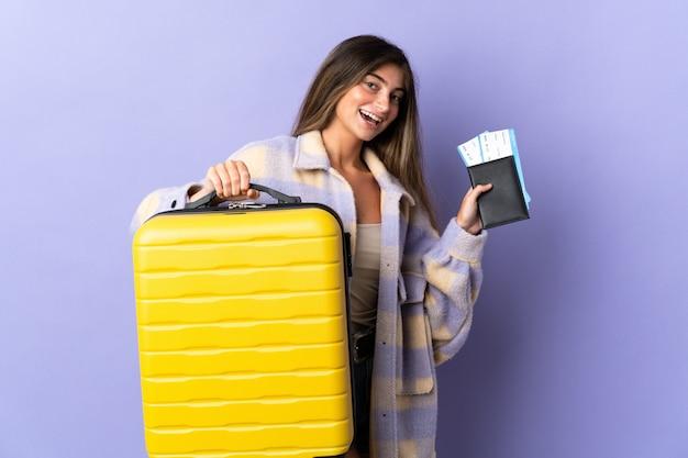 Jovem mulher caucasiana isolada em roxo em férias com mala e passaporte