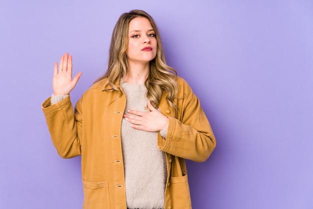 Jovem mulher caucasiana isolada em roxo, prestando juramento, colocando a mão no peito.