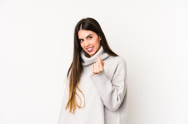 Jovem mulher caucasiana isolada em um branco apontando com o dedo para você como se fosse um convite para se aproximar.