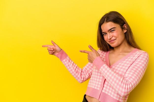 Jovem mulher caucasiana isolada em um fundo amarelo, apontando com os indicadores para um espaço de cópia, expressando entusiasmo e desejo.