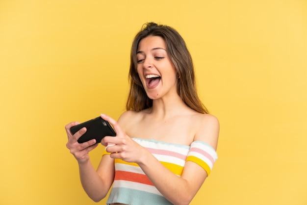 Jovem mulher caucasiana isolada em um fundo amarelo brincando com o celular