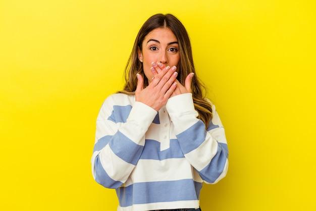 Jovem mulher caucasiana, isolada em um fundo amarelo chocada, cobrindo a boca com as mãos.