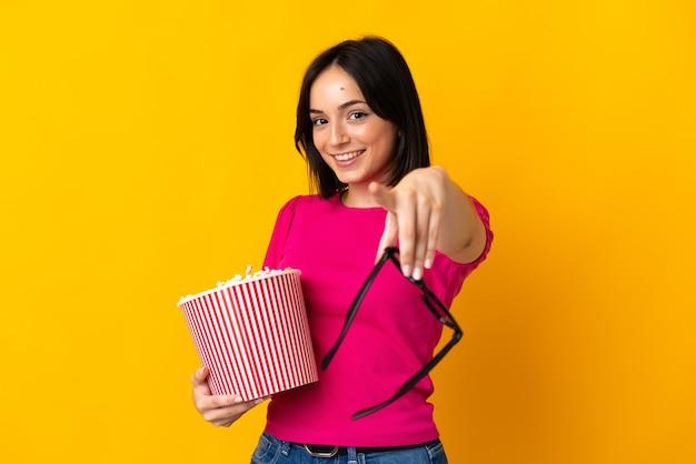 Jovem mulher caucasiana isolada em um fundo amarelo com óculos 3d e segurando um grande balde de pipocas