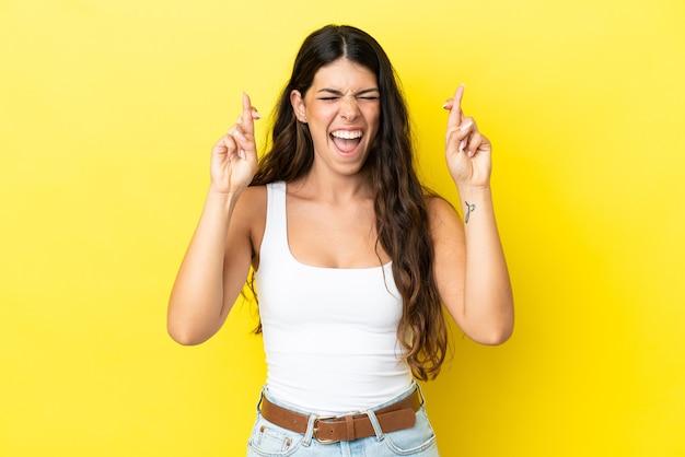 Jovem mulher caucasiana isolada em um fundo amarelo com os dedos se cruzando